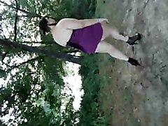 Young BBW with  big hangers walks in the park in high heels